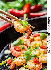 Fried shrimp on chopsticks with herbs