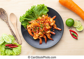 Fried shrimp with pepper and salt in black plate on wooden table, One of famous food in Thailand