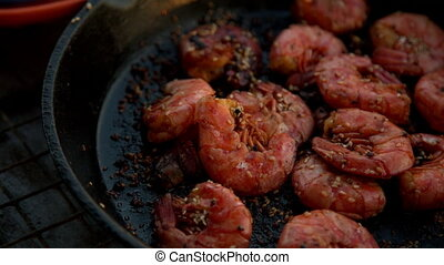 fried shrimps in a pan - the girl takes his hand fried...