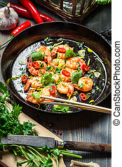 Fried shrimps on pan with fresh herbs