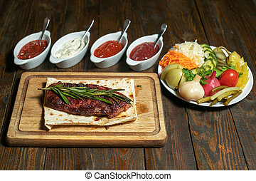 Fried steak with vegetables and sauces on wooden board