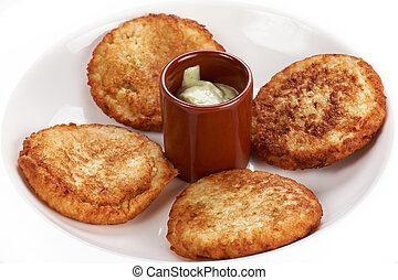 Fried thick pancake with sour cream on a white plate