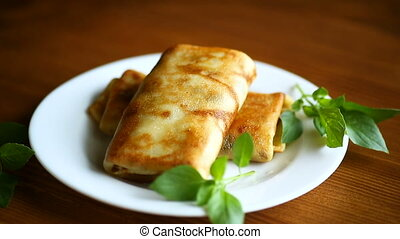 fried thin pancakes stuffed on a plate
