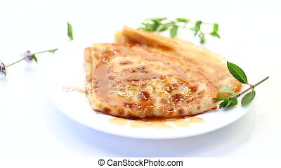 fried thin pancakes with sweet caramel in a plate on a white background