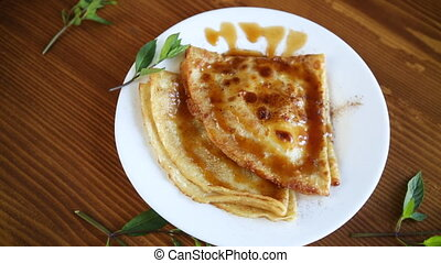 fried thin pancakes with sweet caramel in a plate on a wooden table