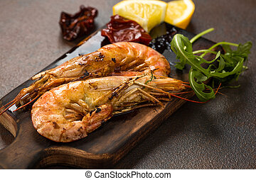 Fried tiger shrimps or langostinos with lemon, arugula, sun dried tomatos on a dark wooden cutting board. Placed on a background of dark table