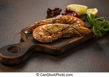 Fried tiger shrimps with lemon, sun-dried tomatoes and greens or rukkola on a dark wooden cutting board.