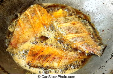 Fried tilapia fish in a frying pan with hot oil