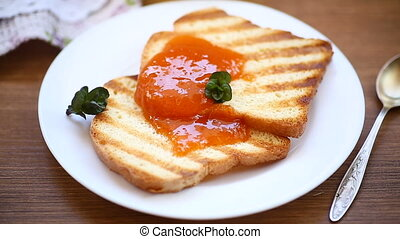 fried toast with apricot jam in a plate on a wooden table