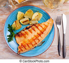 Fried trout fillet with baked potatoes on blue plate
