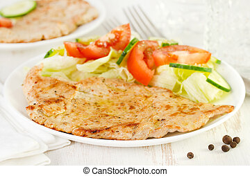 fried turkey with vegetable salad on plate