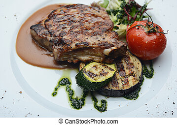 A large piece of roasted veal with tomatoes and courgettes