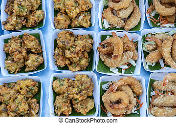 Fried vegetables and shrimps deep-fried is a street food in local market in Thailand, closeup. Thai food