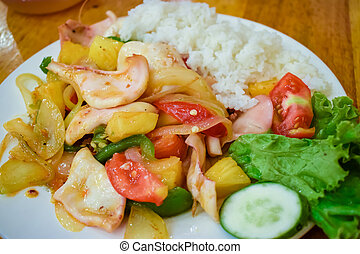 Fried vegetables with seafood and boiled rice on plate