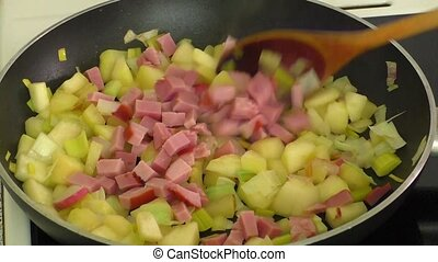 Fried vegetables,ham in a pan