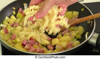 Fried vegetables,pasta,ham in a pan
