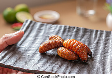 Fried Worm, Insect food with vegetables in the brown bowl. ...