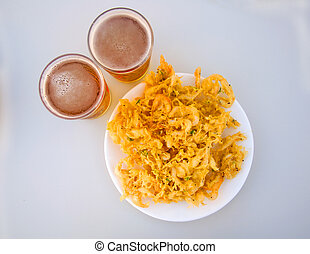 Fried yellow fritters with small shrimps and two beers