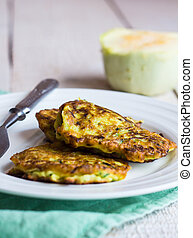 fried zucchini fritters on a white plate, green , white wood...