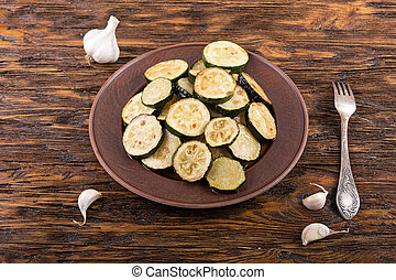 Fried zucchini in a clay plate on a wooden table