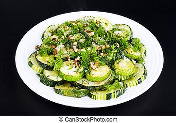 Fried zucchini with green greens, garlic and walnuts.