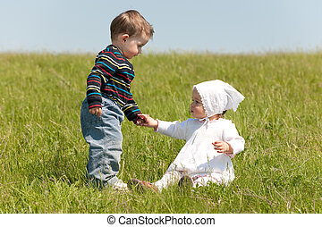 A toddler boy helps a toddler girl to get up in the meadow