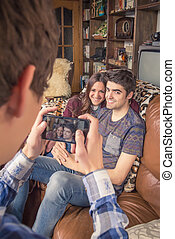 Friend taking photos to teenage couple on a sofa