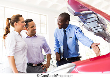 african american vehicle dealer showing couple new car engine