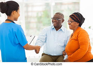 african female nurse greeting senior couple