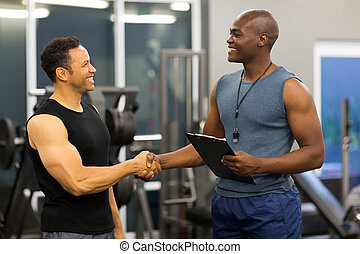 african gym trainer handshaking with mid age client -...