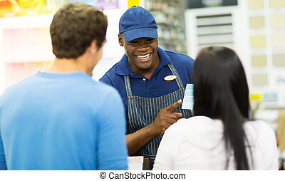 friendly african shop assistant helping couple choose paint color at hardware store