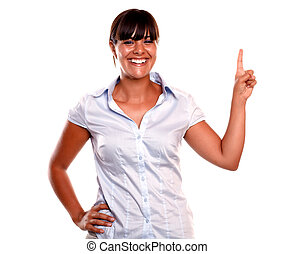 Friendly and smiling young woman pointing up