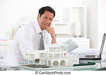 Friendly architect sat at his desk