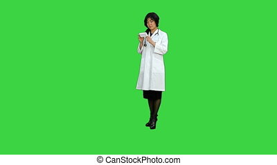 Friendly asian doctor woman working with documents and new pills on a Green Screen, Chroma Key