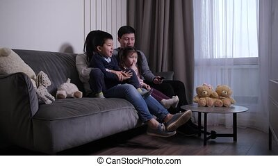 Friendly asian family watching TV in living room - Happy ...