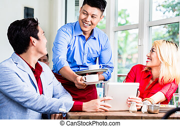 Friendly Asian waiter serving a couple coffee