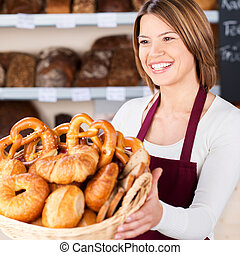 Friendly bakery assistant with a basket filled with an assortment of freshly baked rolls