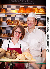 Friendly bakery staff standing behind the counter in a...