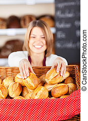 Friendly bakery worker selecting rolls