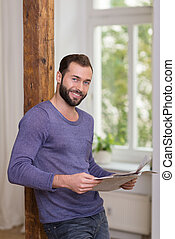 Friendly bearded man relaxing with a newspaper