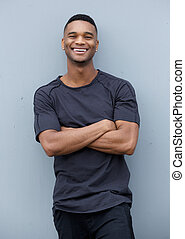 Friendly black man smiling with arms crossed