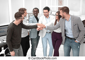 friendly business team putting their hands together