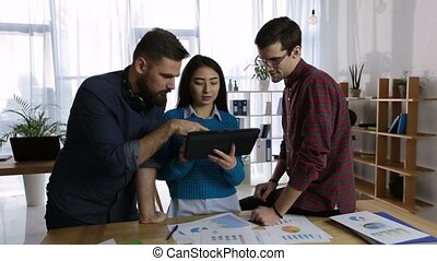 Friendly business team using tablet in office - Confident...