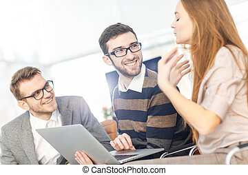 friendly business team working on laptop and discussing business matters