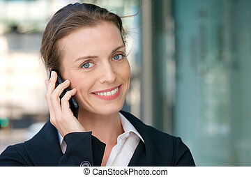 Friendly business woman smiling with mobile phone