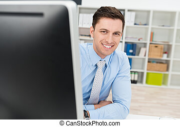 Friendly businessman peering around his computer