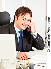 Friendly businessman sitting at office desk and talking on phone
