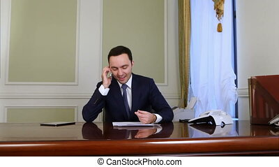 Friendly businessman talking on the phone, laughing and smiling