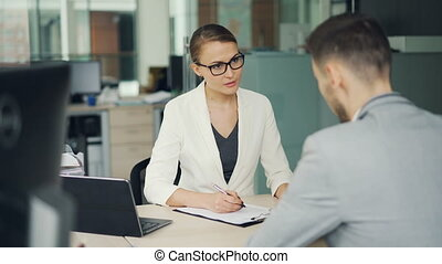 Friendly businesswoman in glasses and suit is interviewing a...