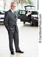 car salesman doing welcoming gesture - friendly car salesman...